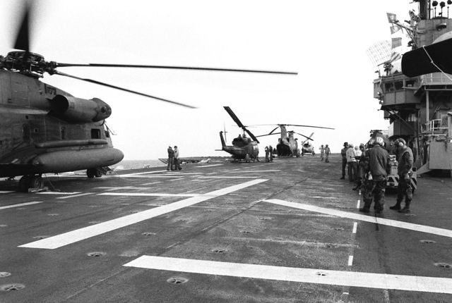 Flight operations take place aboard the amphibious assault ship USS GUAM (LPH 9) off the coast of Grenada during Operation URGENT FURY. Visible on the flight deck are two UH-1N Iroquois helicopters, a CH-46 Sea Knight helicopter and a CH-53 Sea Stallion helicopter