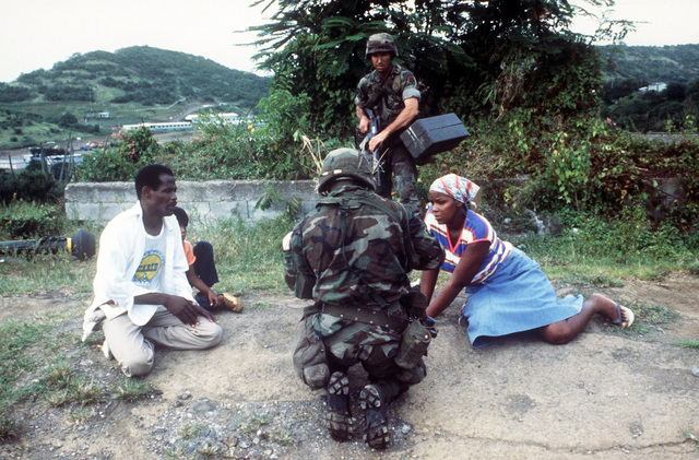 Members of the 82nd Airborne Division encounter residents of the island while on patrol during Operation URGENT FURY