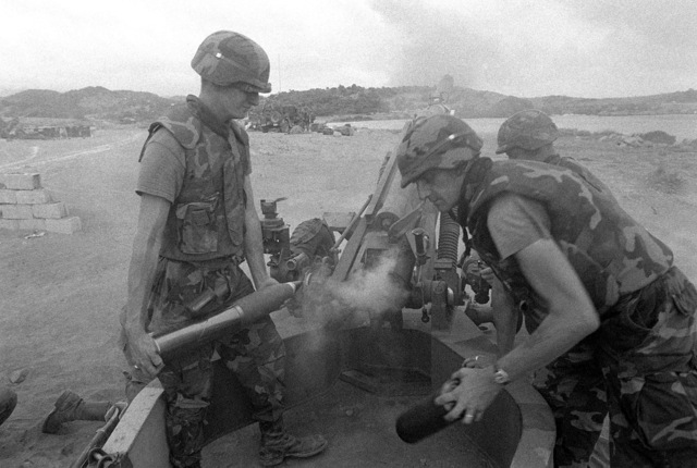 82nd Airborne Division artillerymen reload an M102 105 mm howitzer while providing artillery support for the multiservice, multinational Operation URGENT FURY