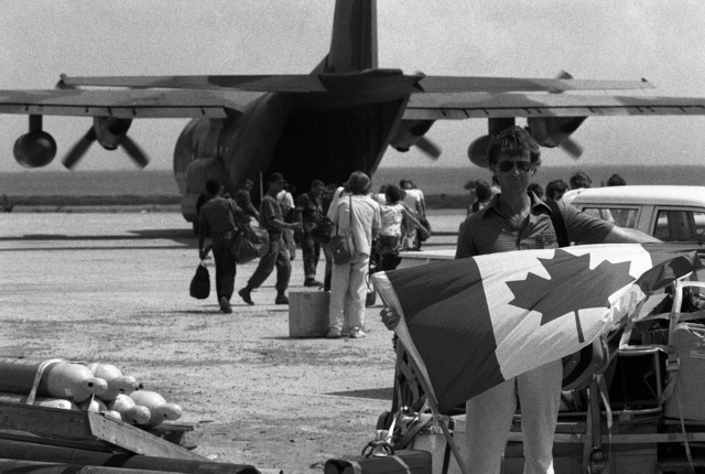 A Canadian national from the Saint George's University School of Medicine displays a Canadian flag prior to boarding a C-130 Hercules aircraft at Point Salines Airfield. He is being evacuated from the island during the multiservice, multinational Operation URGENT FURY