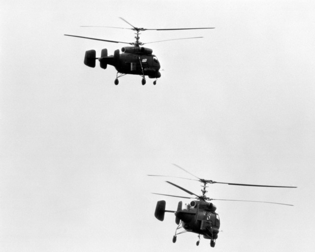 A right rear view of two Ka-25 Hormone helicopters in flight as they conduct anti-submarine warfare operations