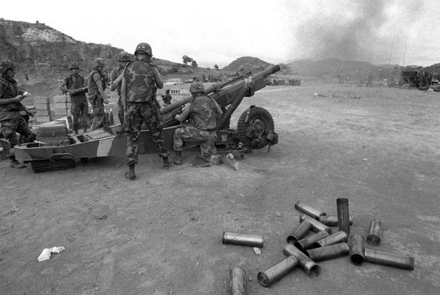 Artillerymen of the 82nd Airborne Division fire an M102 105 mm howitzer while providing artillery support for the multiservice, multinational Operation URGENT FURY