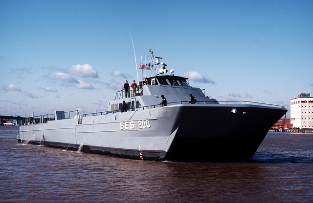 A starboard bow view of the Surface Effect Ship 200 (SES-200) as it is prepared for mooring at a Navy Yard pier. Naval Sea Systems Command procured a 110-foot commercial SES and increased its length by installing a 50-foot hull extension amidships. This was necessary to validate high length-to-beam research