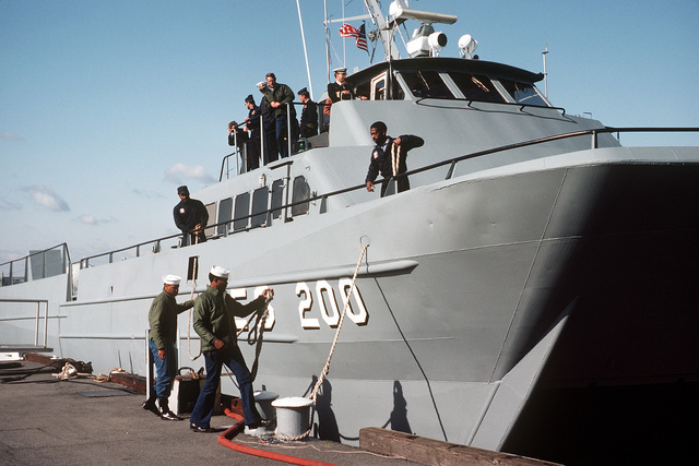 Crewmen moor the surface effect ship 200 (SES-200) to a Navy Yard pier upon its arrival. Naval Sea Systems Command procured a 110-foot commercial SES and increased its length by installing a 50-foot hull extension amidships. This was necessary to validate high length-to-beam research