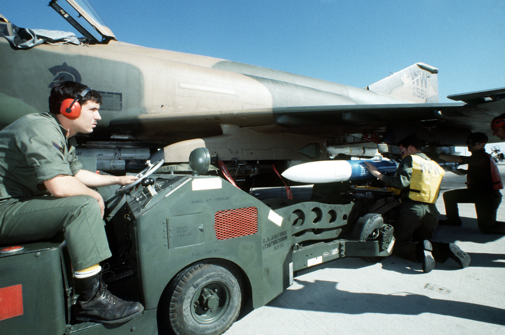 "Munitions personnel load an AGM-45 Shrike missile onto the wing pylon of an F-4G Phantom II ""Advanced Wild Weasel"" aircraft during an operational readiness inspection"
