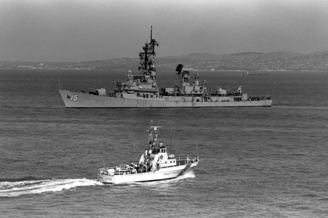 Port side view of the Adams class guided missile destroyer USS BERKELEY (DDG 15). The Coast Guard patrol boat POINT CHICO (WPB 82339) is visible in the foreground