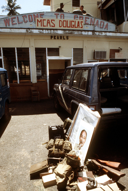 "A portrait of Ho Chi Minh is among material and equipment seized at Pearls Airport during the multi-service, multinational Operation URGENT FURY. Marines unofficially assigned the name ""MCAS Douglas"" to the operations terminal in honor of Sergean Major B. Douglas, a Marine killed in Beirut, Lebanon"