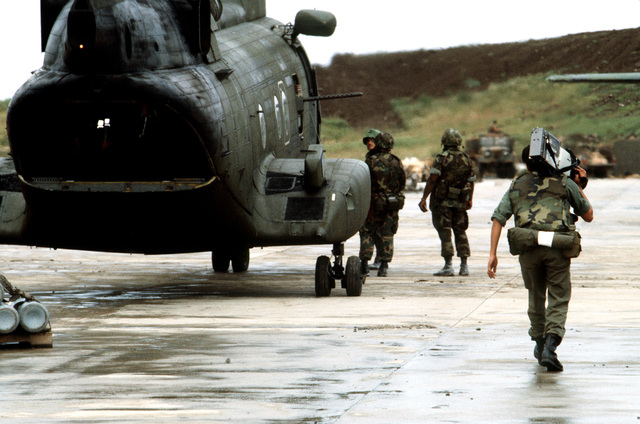 A US Air Force cameraman videotapes activities at Point Salines airfield during the multi-service, multinational Operation URGENT FURY. A CH-46 Sea Knight helicopter is parked on the flight line
