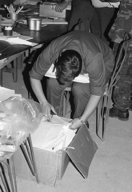 A US serviceman examines paperwork while processing-in members of the US Air Force Special Activities Center (AFSAC) Human Intelligence Resources (HUMINT) Augmentation Team (HAT) during the multiservice, multinational Operation URGENT FURY