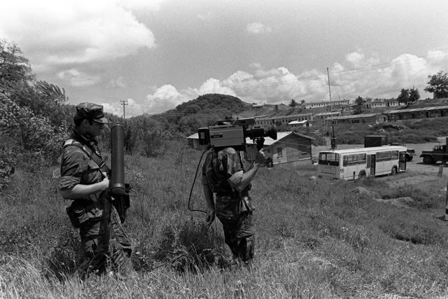 Members of the Navy Combat Camera Team videotape the activities taking place around the airport during Operation URGENT FURY