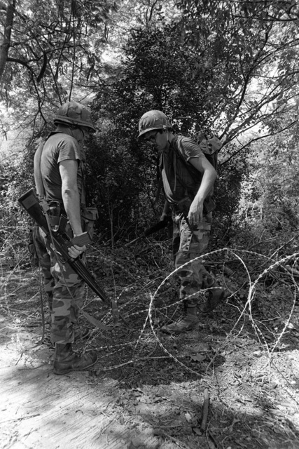 Members of the US Air Force security team examine concertina wire as they patrol the area around the airport during Operation URGENT FURY