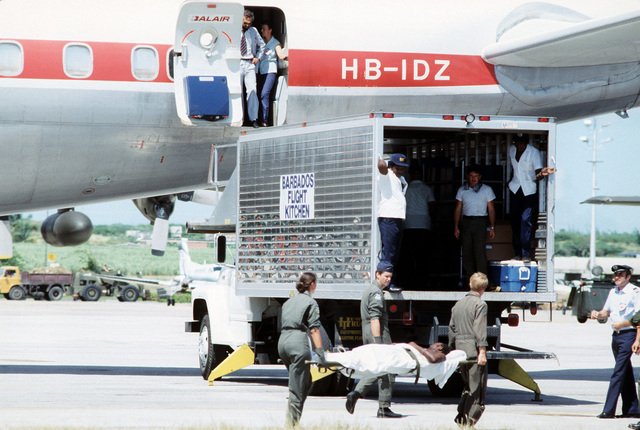 US Air Force personnel assist in loading wounded patients aboard a civilian MEDEVAC aircraft. The patients were wounded during the multiservice, multinational Operation URGENT FURY on Grenada