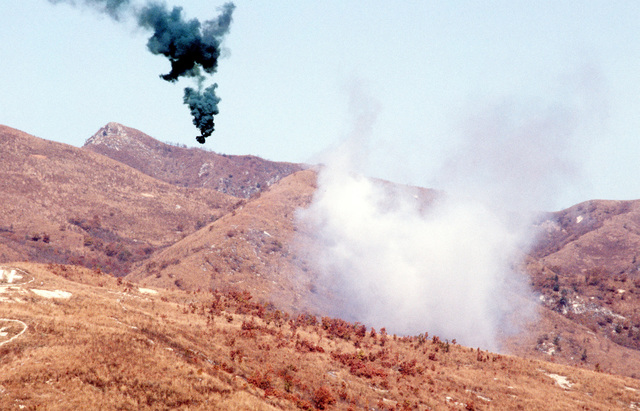 "A green smoke flare is used as ""open-fire"" signal at Nightmare Range during a live-fire exercise for Operation BEAR HUNT '84"