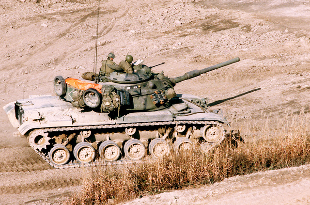An M-60A1 main battle tank maneuvers downrange at Nightmare Range during a live-fire exercise for Operation Bear Hunt '84