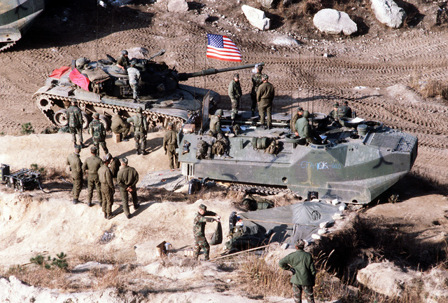 Marines manning an LVTC-7 (tracked landing vehicle, command) relay messages to tanks and LVTP-7s (tracked landing vehicle, personnel) participating in a live-fire exercise during Operation Bear Hunt '84. An M-60A1 main battle tank is parked next to the LVTC-7