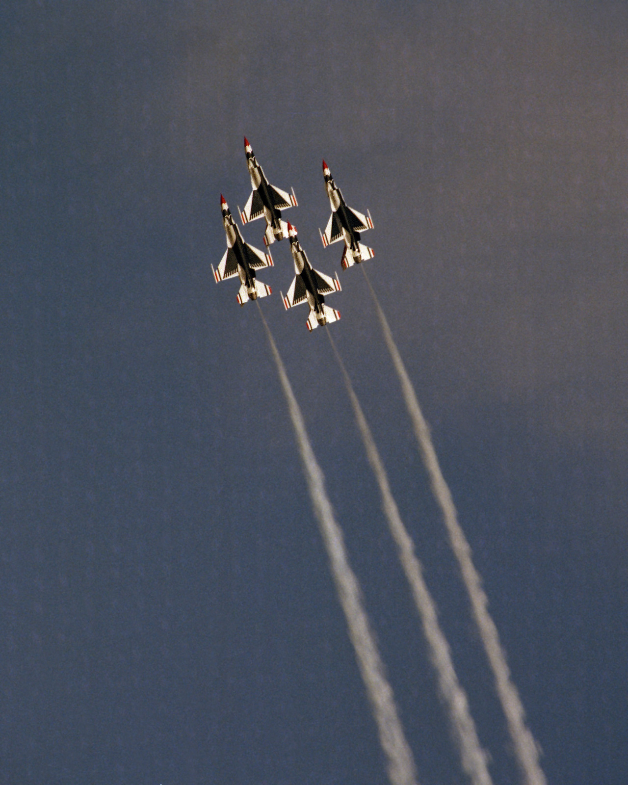 An air-to-air overhead view of four Thunderbirds Air Demonstration Squadron F-16 Fighting Falcon aircraft in a diamond formation during Open House '83
