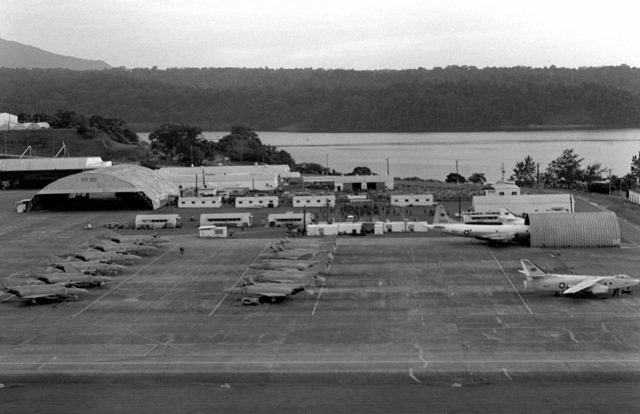 Aerial view of the runway apron at Arthur W. Radford Field. Several F-4 Phantom II aircraft are parked on the left. An A-3D Skywarrior aircraft is on the right. A P-3 Orion aircraft is parked in a hangar