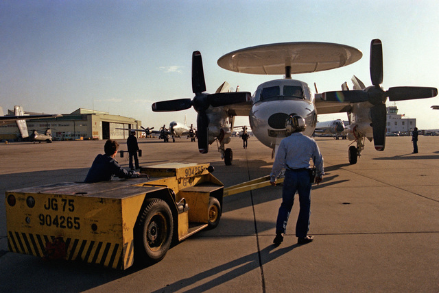 A ground crewman positions a TA-75 tow tractor in front of an Airborne Early Warning Squadron 78 (VAW-78) E-2C Hawkeye aircraft parked on the flight line at Naval Air Station, Norfolk