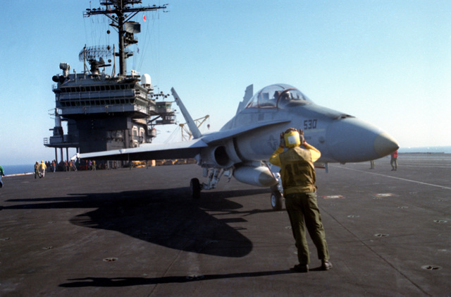 A plane director signals to the pilot of an F/A-18 Hornet aircraft aboard the aircraft carrier USS KITTY HAWK (CV 63). The aircraft is assigned to Strike Fighter Squadron 125 (VFA-125)
