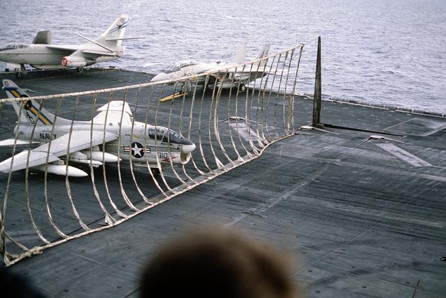 An Attack Squadron 66 (VA-66) A-7E Corsair II aircraft engages the nylon webbing of a barricade during an emergency landing aboard the nuclear-powered aircraft carrier USS DWIGHT D. EISENHOWER (CVN 69)
