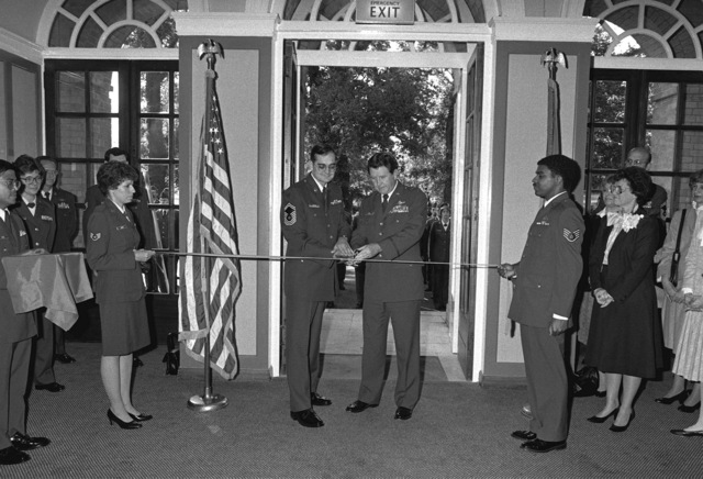 Major General William P. Acker and the commandant of the Non-commissioned Officer's Leadership School (NCOLS) cut the ribbon to open the school's new location. The NCOLS was recently moved from Royal Air Force Wethersfield and the first class is scheduled  to graduate on November 15, 1983