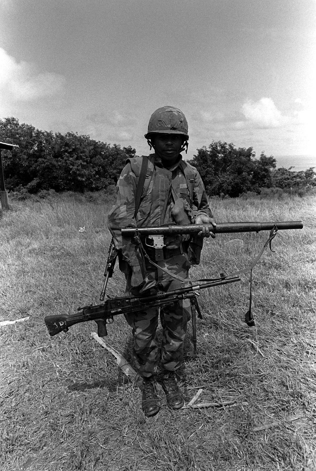 A Marine Displays Seized Soviet RPG 2 Rocket Launcher And Bren Light Machine Gun After Arriving With Battalion Landing Team During Operation Urgent