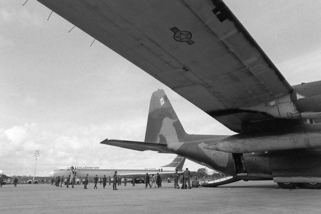 A US Air Force security police stand guard as Cuban nationals are transferred from a C-130 Hercules aircraft to a Cuban I1-62M airliner that will return them to Cuba. They were captured on Grenada during the multiservice, multinational Operation URGENT FURY