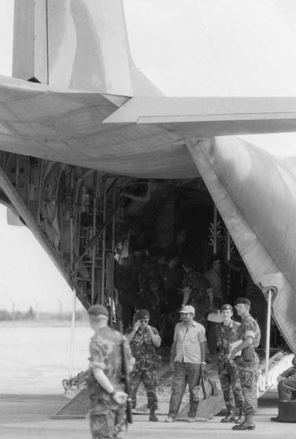 A US Air Force security police stand guard as Cuban nationals exit from a C-130 Hercules aircraft. An airliner is waiting nearby to transport them back to Cuba. They were captured on Grenada during the multiservice, multinational Operation URGENT FURY