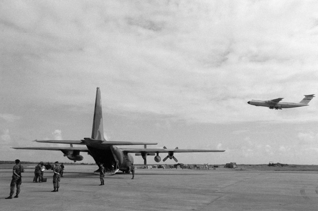 A US Air Force security police stand guard as Cuban nationals exit from a C-130 Hercules aircraft. An airliner is waiting nearby to transport them back to Cuba. They were captured on Grenada during the multiservice, multinational Operation URGENT FURY. A US Air Force C-141B Starlifter aircraft takes off in the background