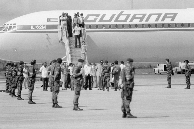 A US Air Force security police stand guard as Cuban nationals prepare to board a Cuban I1-62M airliner that will return them to Cuba. They were captured on Grenada during the multiservice, multinational Operation URGENT FURY