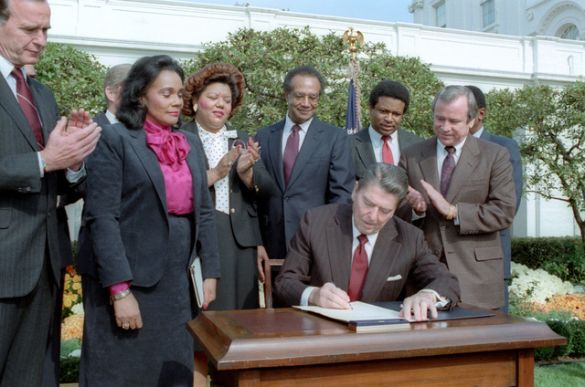 President Reagan at Signing Ceremony for Martin Luther King Holiday Legislation in the Rose Garden with Coretta Scott King, George Bush, Howard Baker, Bob Dole, Jack Kemp, Samuel Pierce, Katie Hall Looking on