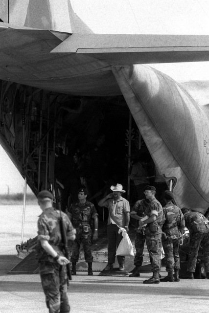 U.S. Air Force Security police stand guard as Cuban nationals exit from a C-130 Hercules aircraft. A Cuban airliner is waiting nearby to transport them back to Cuba. The Cubans were captured on Grenada during the multiservice, multinational Operation Urgent Fury