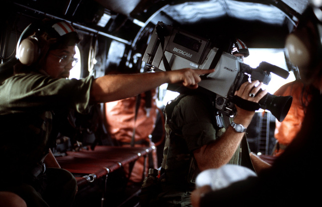 An audiovisual crew videotapes Operation URGENT FURY from a helicopter in flight