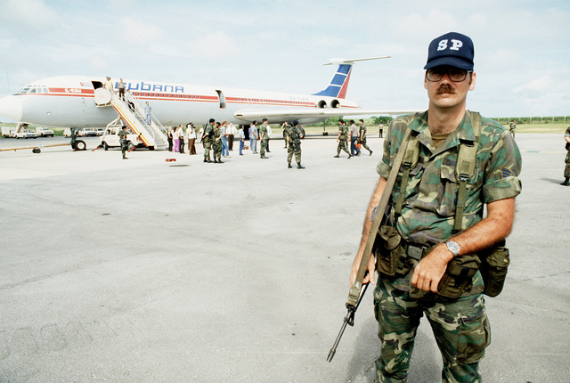 U.S. Air Force Security police stand guard as Cuban nationals board an I1-62M airliner for return to Cuba. They were captured on Grenada during the multiservice, multinational Operation Urgent Fury