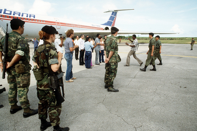 U.S. Air Force Security police stand guard as Cubans are transferred from a C-130 Hercules aircraft to a Cuban I162M aircraft for the trip back to their country during Operation Urgent Fury