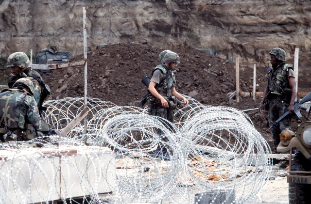 US military personnel, armed with M16A1 rifles, lay concertina wire during Operation URGENT FURY