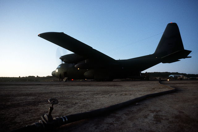 A fuel hose is connected to C-130 Hercules aircraft to offload fuel during Operation Urgent Fury