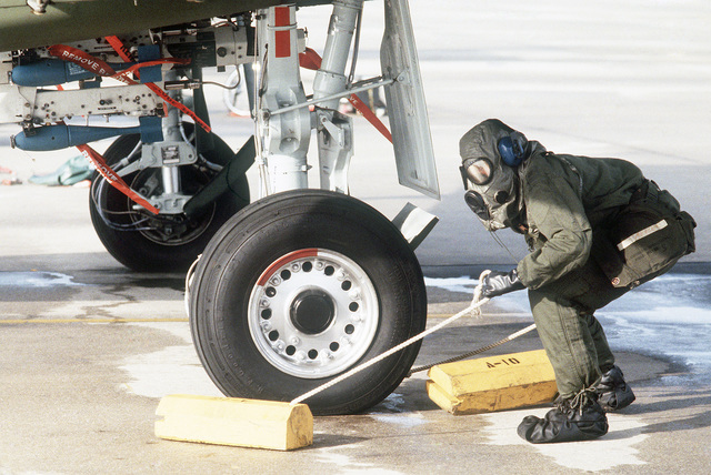 A member of the 354th Tactical Fighter Wing, wearing M-17 chemical-biological field masks, removes a wheel chock from under an A-10 Thunderbolt II aircraft during Exercise THUNDERHOG V