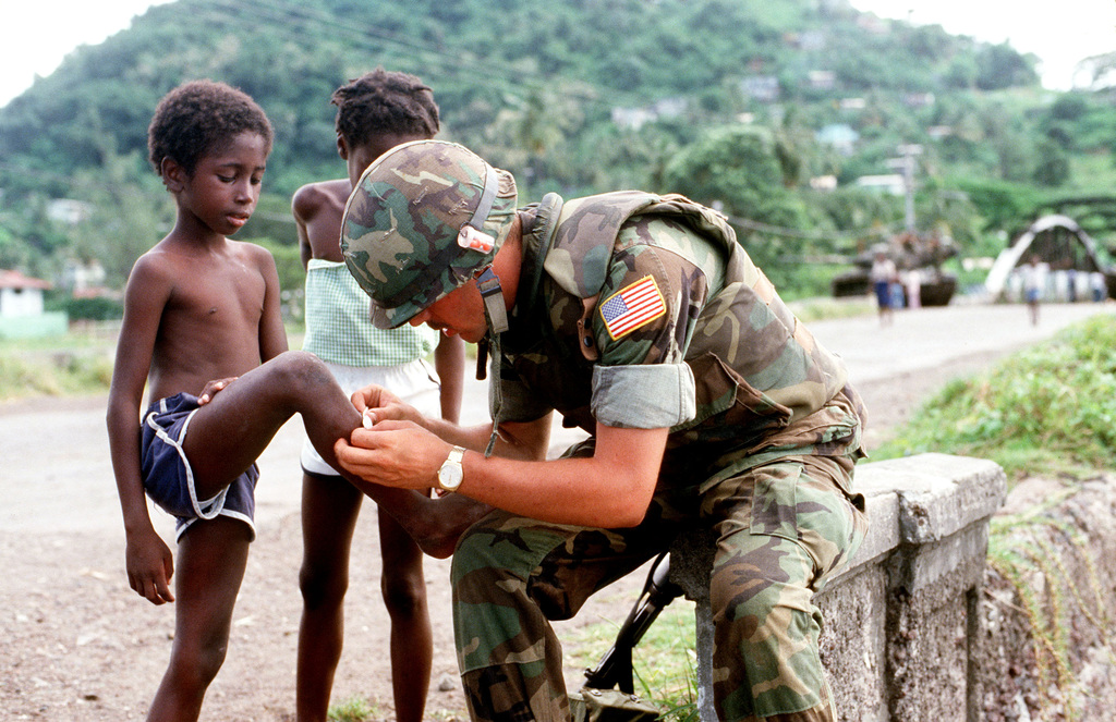 A US serviceman applies a band-aid to a Grenadian child's leg during Operation URGENT FURY