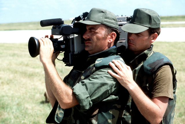 An audio-visual team videotapes activities at Point Salines airfield during the multi-service, multinational Operation URGENT FURY