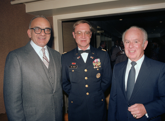 Former members of the US Army Audiovisual Center (USAAVC), retired Lieutenant Colonel (LTC) Jon De. Vitto, left, and retired LTC Walter T. Halloran, right, pose for a picture with James T. Van Orden Jr., during the unit's 40th anniversary celebration at the Arlington Hall Station Officers Club