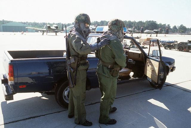 Members of the 354th Security Police Squadron, wearing M-17 chemical-biological field masks, participate in a nuclear-biological-chemical (NBC) warfare exercise during THUNDERHOG V. The airman on the left is armed with an M16 rifle