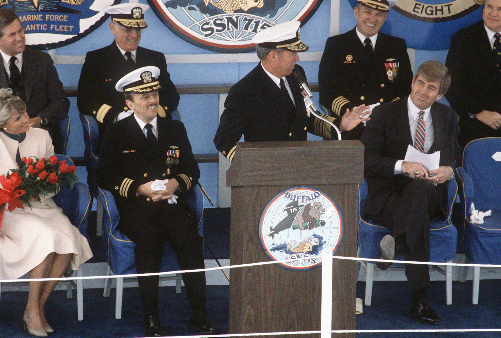 Admiral (ADM) Wesley L. McDonald, commander in chief, Atlantic and Atlantic Fleet, speaks during the commissioning ceremony for the nuclear-powered attack submarine USS BUFFALO (SSN 715). Representative Jack F. Kemp (Republican-New York) is seated on the right. On the left are Commander (CDR) G. Michael Hewitt, commanding officer of the BUFFALO, and Commodore M. MacKinnon, supervisor of Shipbuilding, Conversion and Repair, Newport News Shipbuilding
