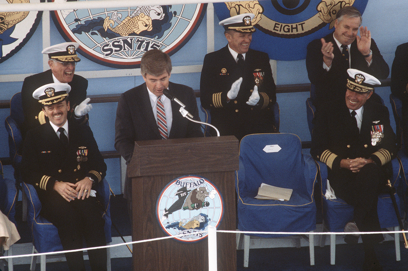 Representative Jack F. Kemp (Republican-New York) speaks during the commissioning ceremony for the nuclear-powered attack submarine USS BUFFALO (SSN 715). Admiral (ADM) Wesley L. McDonald, commander in chief, Atlantic and Atlantic Fleet, is seated on the right. On the left are Commander (CDR) G. Michael Hewitt, commanding officer of the BUFFALO, and Commodore Malcolm MacKinnon, supervisor of Shipbuilding, Conversion and Repair, Newport News Shipbuilding
