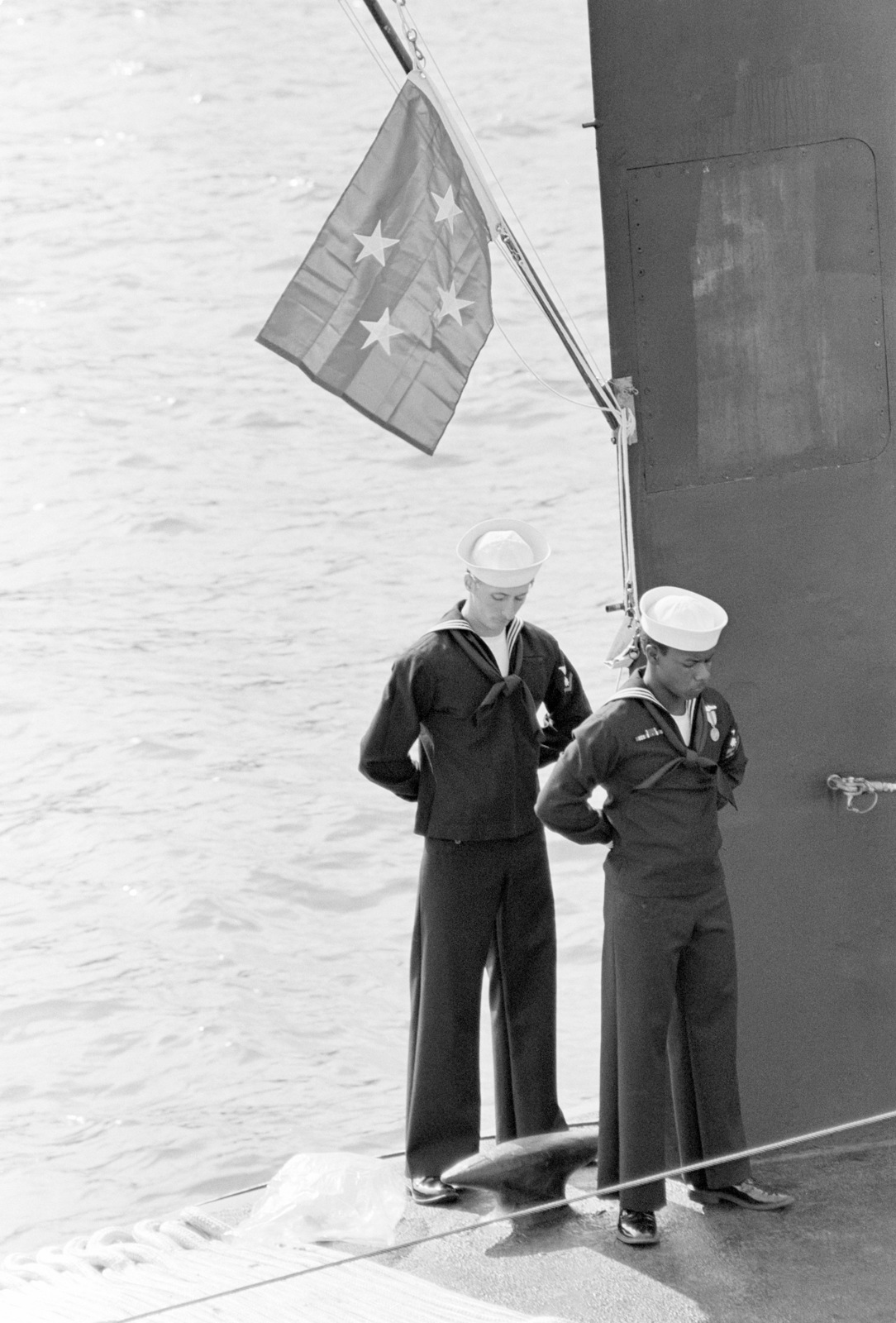 Two crewmen stand under the personal flag of Admiral Wesley L. McDonald, commander in chief, Atlantic and Atlantic Fleet, as it flies from the sail of the nuclear-powered attack submarine USS BUFFALO (SSN 715) during the ship's commissioning ceremony