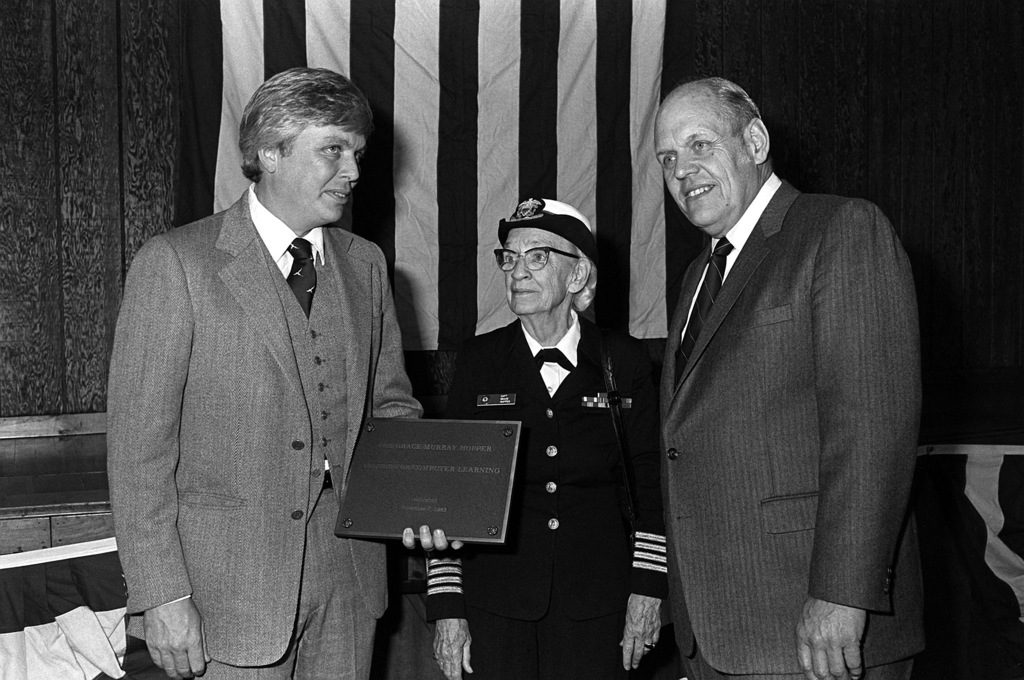 Captain Grace Murray Hopper is presented with a plaque by David M. Smith, left, headmaster of Brewster Academy, as Kenneth Olsen, founder and president of Digital Corp., looks on, at the ceremony to dedicated a computer learning center in her name at the high school