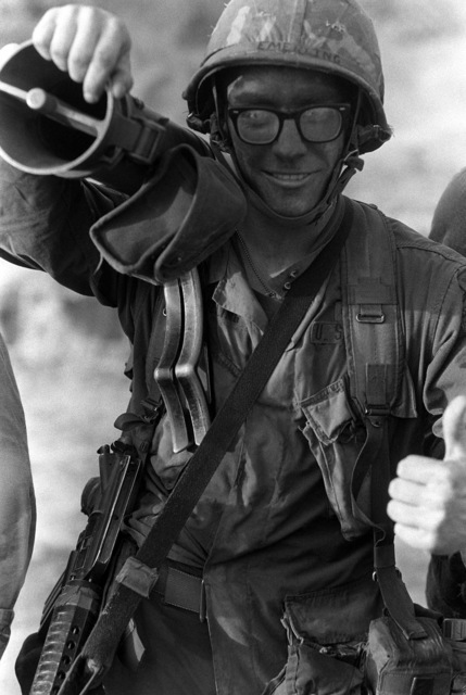 """A US infantryman gives the """"The Thumbs Up"""" sign during his participation in Operation URGENT FURY. He is carrying a 90 mm M67 recoilless rifle on his shoulder"""