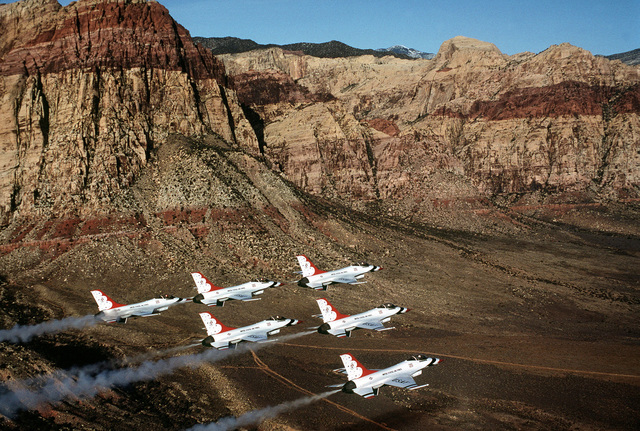 An air-to-air right side view of six F-16 Fighting Falcon aircraft assigned to the Thunderbirds flight demonstration team, during an air show over Nellis Air Force Base