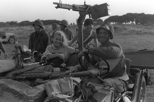 An American woman sits in the front seat of an M151A1 1/4-ton light vehicle with a US military infantryman prior to being evacuated from the island during Operation URGENT FURY. The vehicle has an M60 machine gun mounted on it, and another M60 is on the right side of the hood with an M203 grenade launcher mounted on an M16A1 rifle on the left