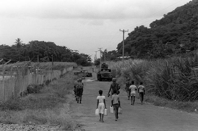 Grenadian children walk down a road behind US infantrymen during Operation URGENT FURY